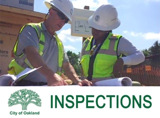 Photo of building inspectors looking at project plans at job site