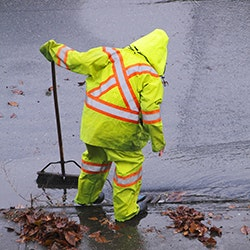 Photo of Person cleaning storm drain in rain